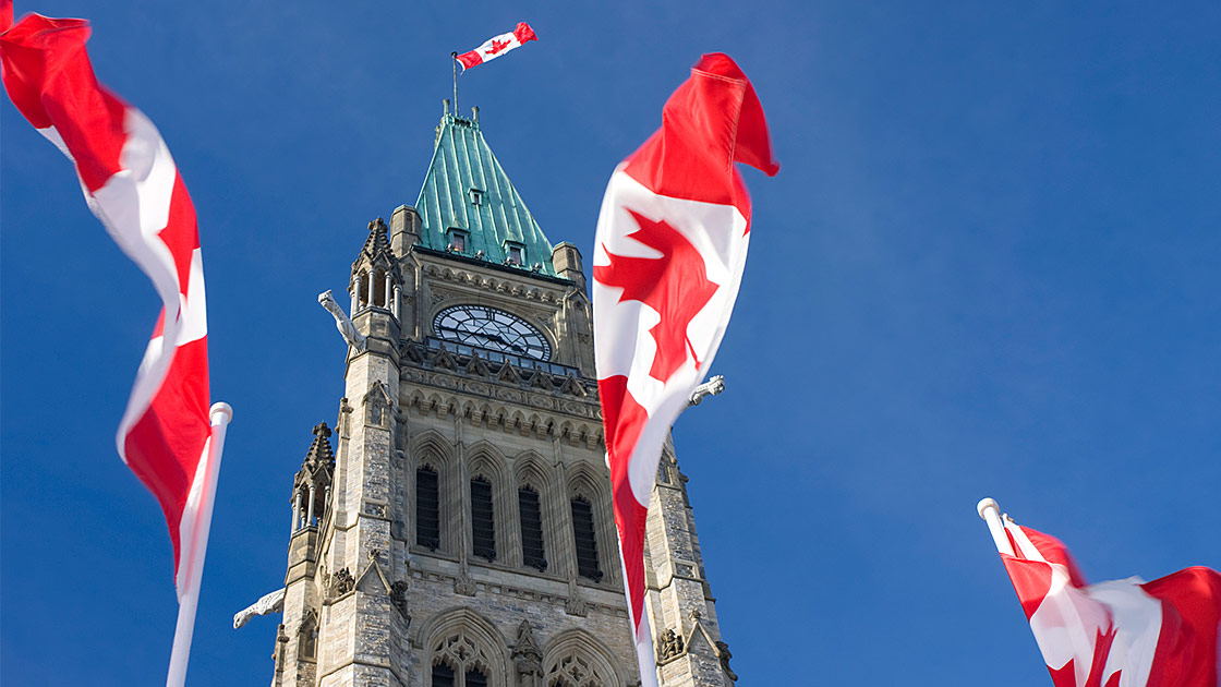 Image of Parliament of Canada building with three Canadian flags in the background