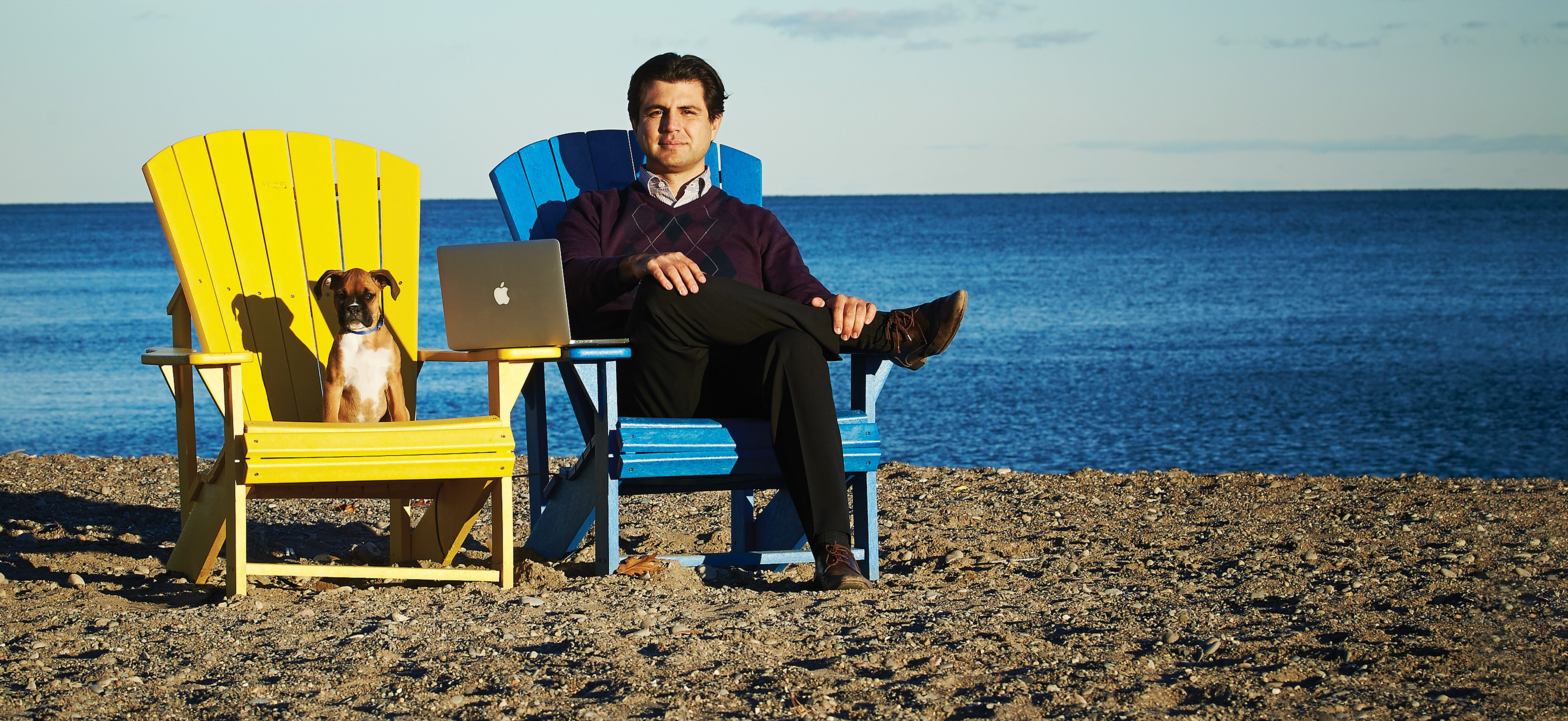 A man sits with his dog and his laptop on a chair on a beach.