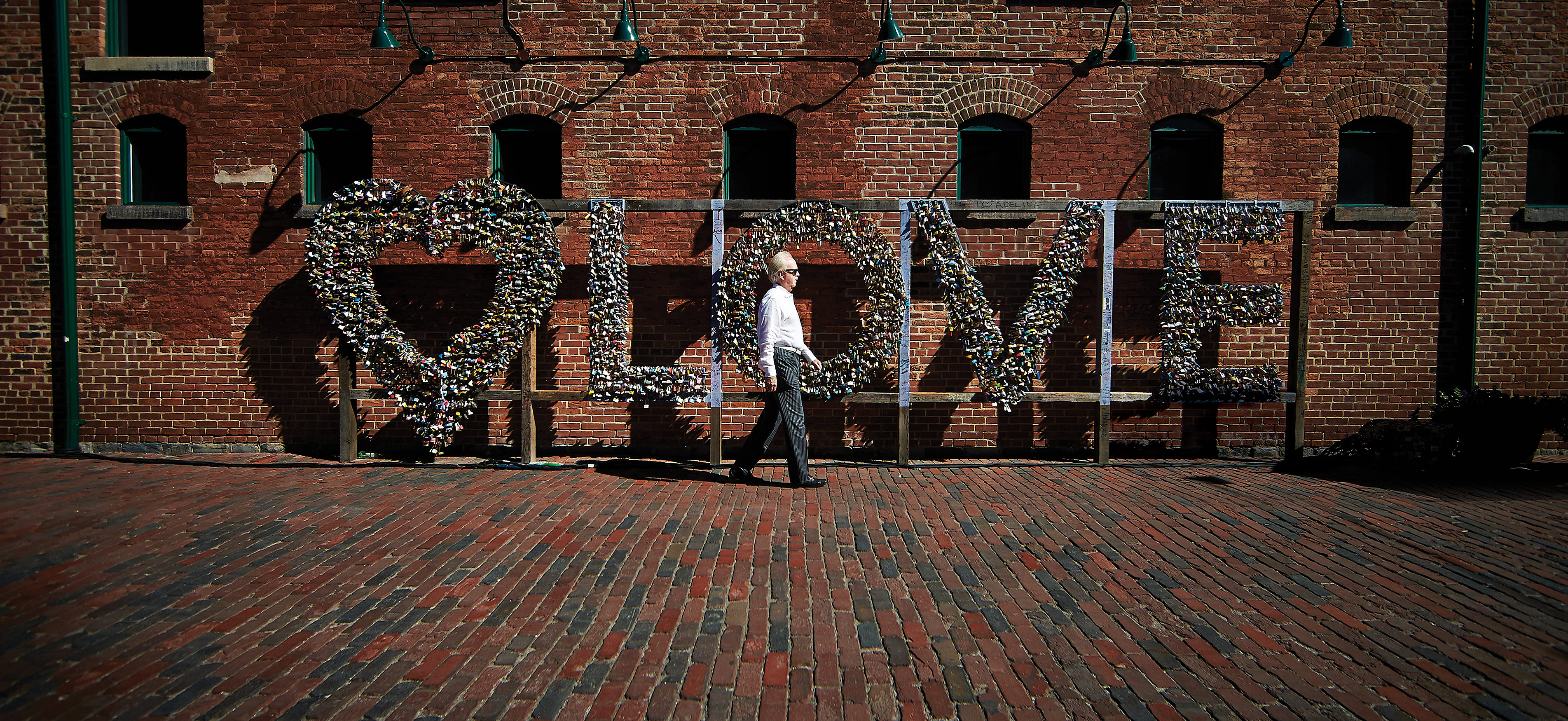 Ivey alum John Brownlee walks in front of the love lock installation in the Distillery District in Toronto.