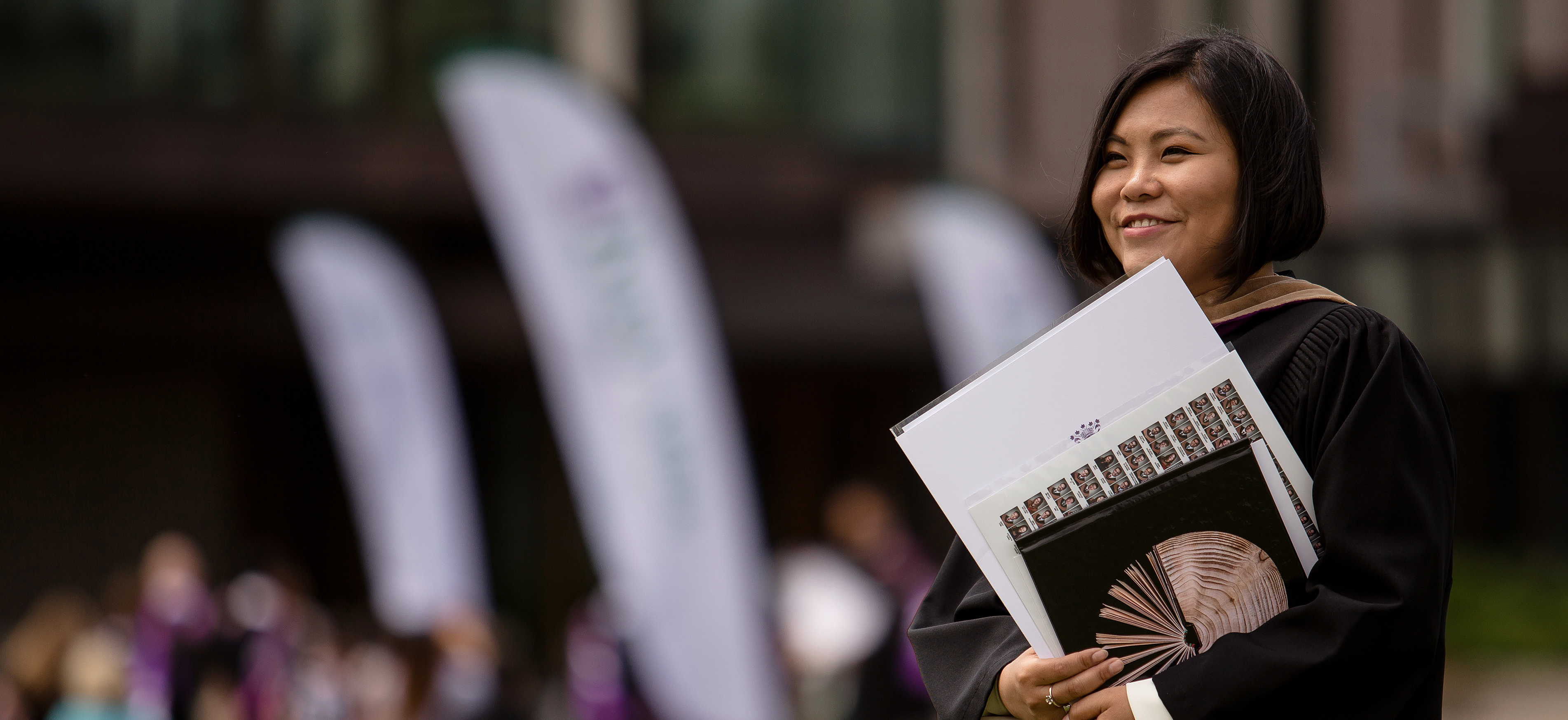 A woman dressed in a graduation gown and holding her Ivey degree stands in front of the Ivey Building at Convocation.