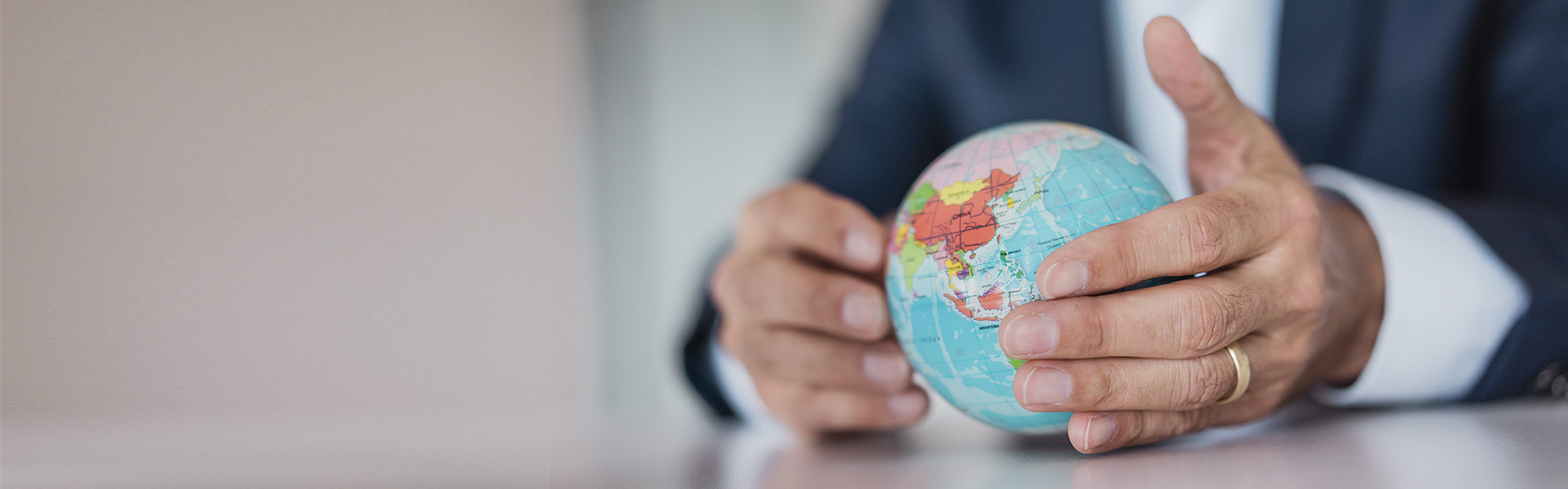 Close-up of hands of businessman holding globe.