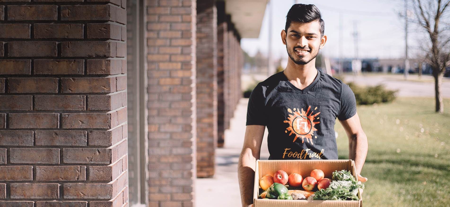 Divyansh Ojha, a 20-year-old student, stands outside with a cardboard box of fruits and vegetables.
