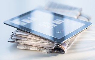 An iPad sitting on a stack of newspapers