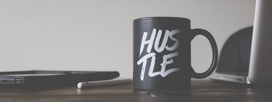 Close up of a coffee mug with the word Hustle on it